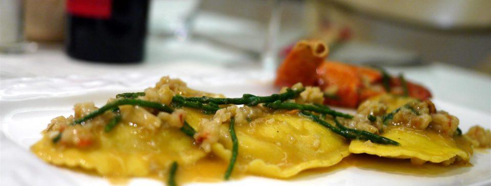 Ravioli ripieni di branzino, con con sugo di gamberi, arancia e salicornia